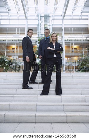 Full length portrait of confident business people standing outside office - stock photo