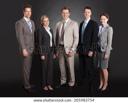 Full length portrait of confident business team standing arms crossed against black background - stock photo