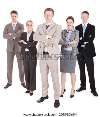 Full length portrait of confident business team standing arms crossed against white background