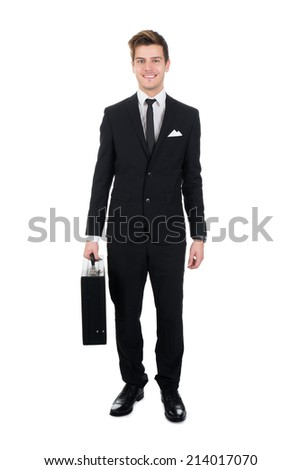 Full length portrait of confident businessman carrying briefcase over white background - stock photo