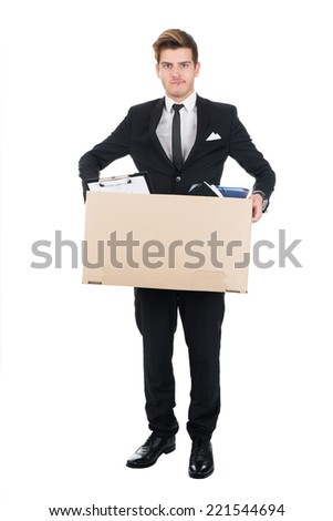 Full length portrait of confident businessman carrying cardboard box against white background - stock photo