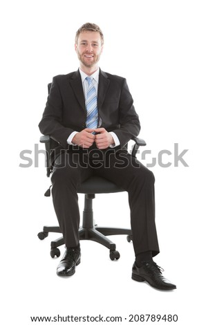 Full length portrait of confident businessman sitting on office chair over white background - stock photo