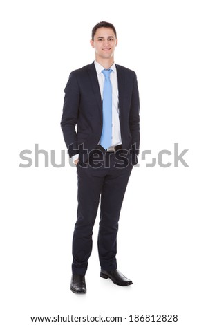 Full length portrait of confident businessman standing with hands in pockets against white background