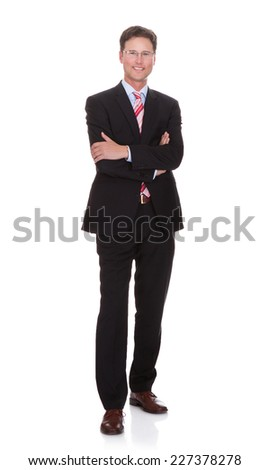 Full length portrait of confident businessman with arms crossed standing against white background - stock photo