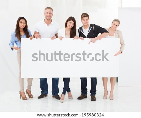Full length portrait of confident businesspeople holding blank billboard in office - stock photo