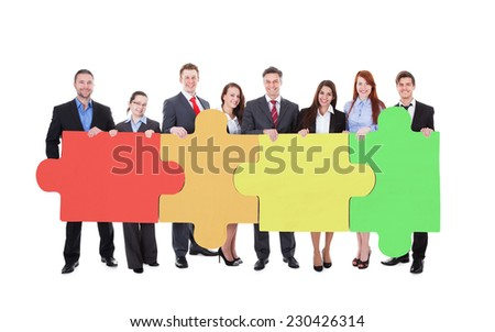 Full length portrait of confident businesspeople joining jigsaw puzzle pieces against white background - stock photo