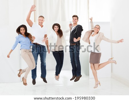 Full length portrait of confident businesspeople jumping with arms raised in office - stock photo