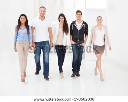 Full length portrait of confident businesspeople walking together in office - stock photo
