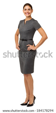 Full length portrait of confident businesswoman with hands on hips standing over white background. Vertical shot. - stock photo