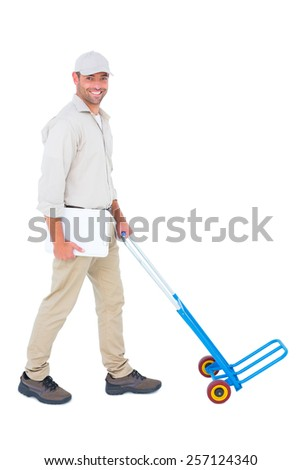 Full length portrait of confident delivery man pushing empty trolley on white background - stock photo