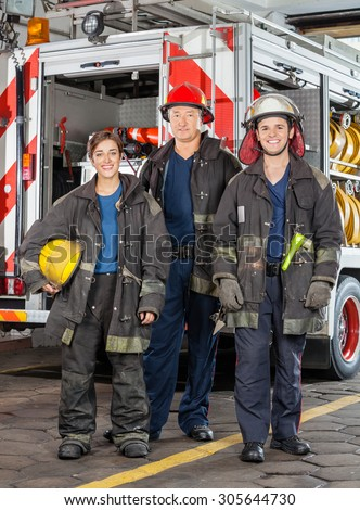 Full length portrait of confident firefighters standing against truck at fire station - stock photo