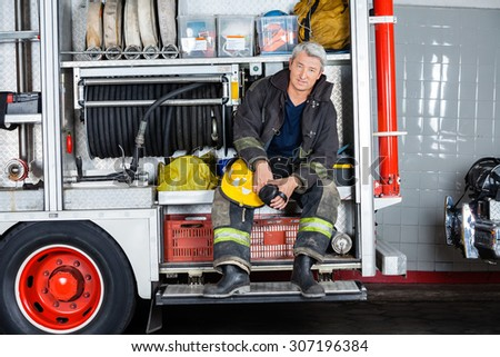 Full length portrait of confident fireman sitting in truck at fire station - stock photo