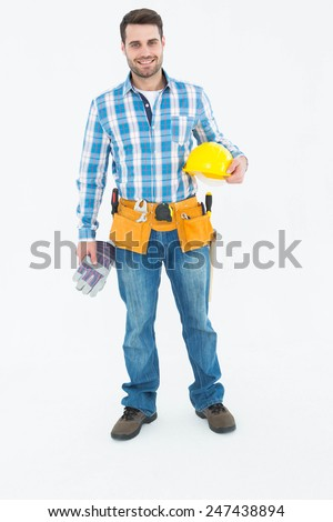 Full length portrait of confident handyman holding hard hat and gloves on white background - stock photo