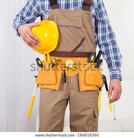 Full length portrait of confident male repairman holding drill machine in living room - stock photo