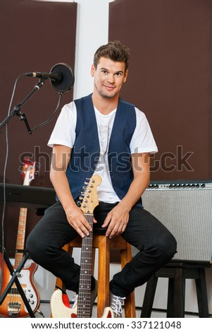 Full length portrait of confident man holding guitar while sitting on stool in recording studio - stock photo