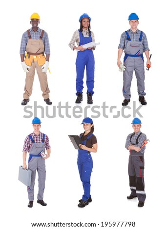 Full length portrait of confident manual workers standing against white background - stock photo
