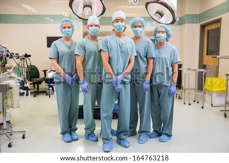 Full length portrait of confident medical team standing in operation room