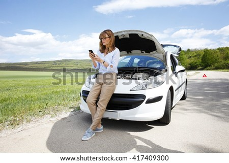 Full length portrait of confident middle aged woman using her mobile phone while standing on the road at her broken down car. - stock photo