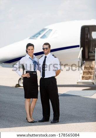 Full length portrait of confident stewardess and pilot standing against private jet at terminal - stock photo