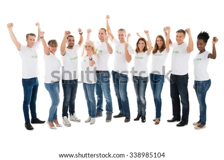 Full length portrait of confident volunteers with arms raised standing in row against white background