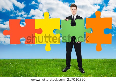 Full length portrait of confident young businessman solving jigsaw puzzle on field against cloudy sky - stock photo