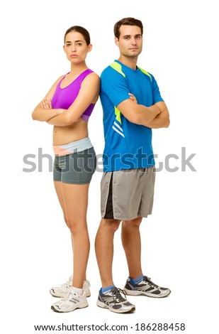 Full length portrait of confident young couple in sports wear standing back to back over white background. Vertical shot. - stock photo
