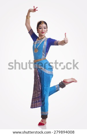 Full length portrait of confident young woman performing Bharatanatyam over white background - stock photo