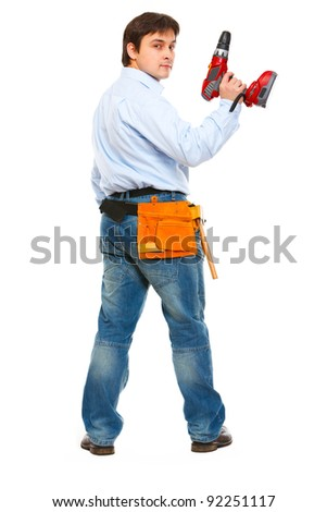 Full length portrait of construction worker with drill look back