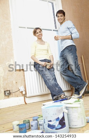 Full length portrait of couple holding coffee mugs while leaning on window in unrenovated house