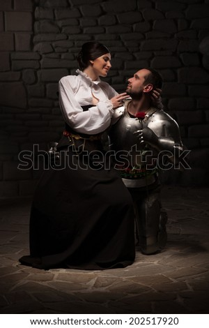 Full length portrait of couple in historical costumes, medieval knight giving rose to beautiful brunette lady sitting on his knee, on dark background