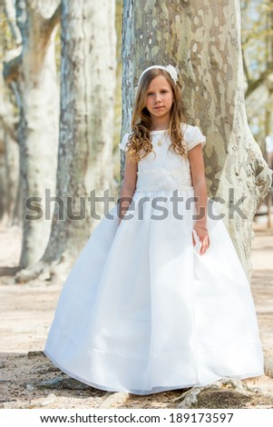 Full length portrait of cute girl in white dress in forest.