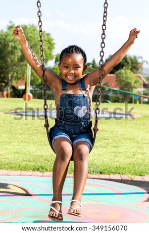 Full length portrait of cute Little african child swinging in park.