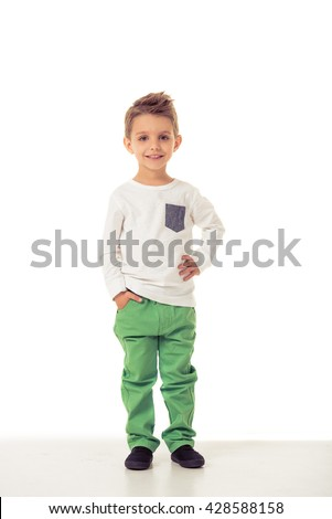 Full length portrait of cute little boy in stylish clothes looking at camera and smiling while standing with hand in pocket, isolated on a white background - stock photo
