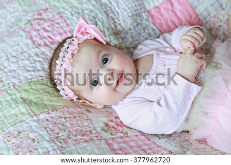 full length portrait of cute little girl toddler in a rose dress lying on plaid, 6 month, studio. Girl is laughing and wondering - stock photo
