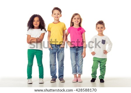 Full length portrait of cute little kids in casual clothes looking at camera and smiling, isolated on a white background
