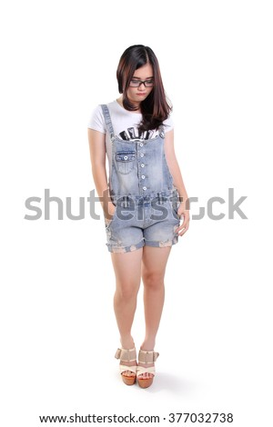 Full length portrait of cute sad nerdy girl looking down, isolated on white background - stock photo