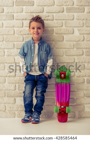 Full length portrait of cute stylish little boy in jeans looking at camera and smiling, standing with hands in pockets against white brick wall - stock photo