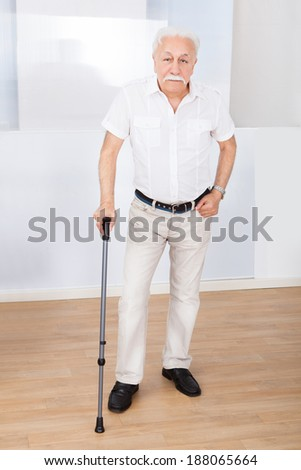 Full length portrait of disabled senior man with walking stick standing at nursing home