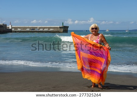 Full length portrait of elderly woman that is standing on black volcanogenic sand of Guios beach with beach wrap in hands on surf waves background in Los Gigantes, Tenerife, Canary Islands. - stock photo