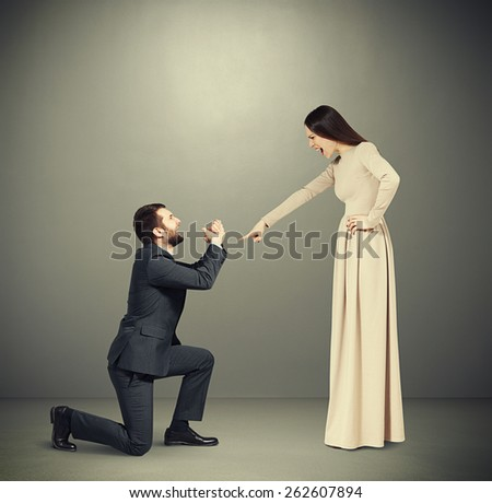 full length portrait of emotional couple over grey background. angry woman pointing and screaming at man, man standing on knee and apologizing - stock photo