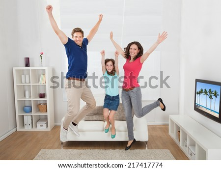Full length portrait of excited family with arms raised jumping in living room at home - stock photo
