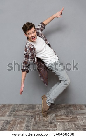 Full length portrait of excited happy cheerful positive handsome dancing young man in plaid shirt isolated on white background - stock photo