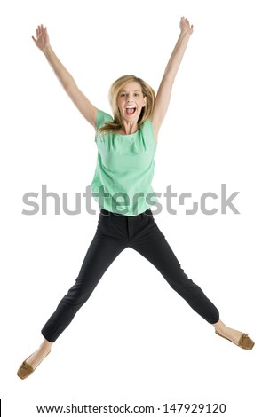 Full length portrait of excited young woman with arms raised in mid-air isolated against white background - stock photo