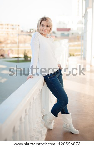 Full length portrait of fashion young blond woman with short hair posing in white leaning against column. Series.