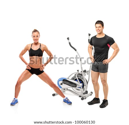 Full length portrait of female and male athletes posing next to a cross trainer machine isolated on white background - stock photo