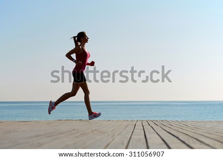 Full length portrait of female athlete doing an active fitness training on the wooden pier against beach, young sportswoman with good figure doing exercises for muscles of body during an active run
