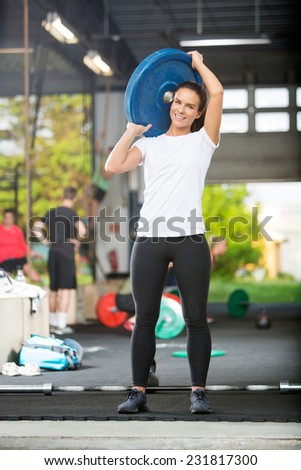 Full length portrait of fit woman lifting barbell plate - stock photo