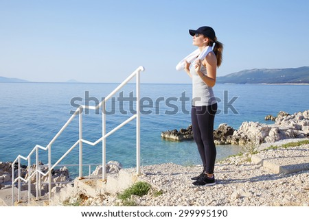 Full length portrait of fit woman standing on the rock by the sea after early morning running. Sporty woman relaxing by the seaside.  - stock photo