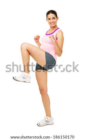 Full length portrait of fit young woman Zumba dancing over white background. Vertical shot. - stock photo
