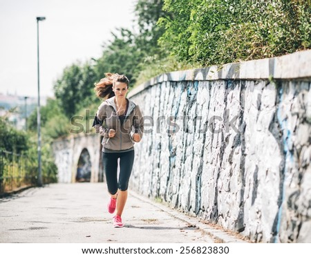 Full length portrait of fitness young woman jogging in the city park - stock photo